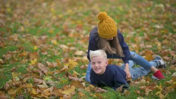 Dětství. Happy Children Have Fun in the Autumn Park. Děti hrají Sedět na podzim padlých listí v parku.