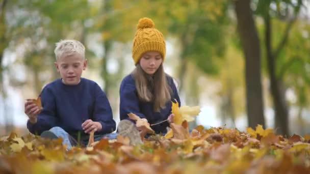 Šťastné roztomilé děti baví v podzimním parku. Děti sbírat kytice krásné žluté padlé listy. Dětství.