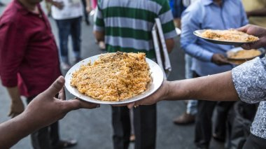 hand is passing a plate a rice to a community member as a iftar meal at the end of a day of fasting
