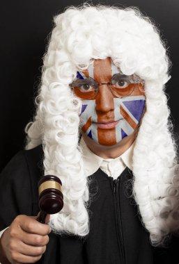 Portrait of male english lawyer with painted British Union Jack flag holding judge gavel on black