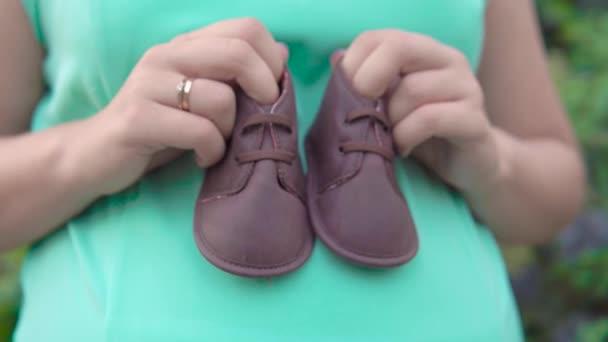 terhes lány tartja a kezében a háttérben a zöld bokrok gyermekcipőt