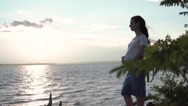 Pregnant woman touching her belly at sunset.close-up of a pregnant woman in a striped dress on the background of a river