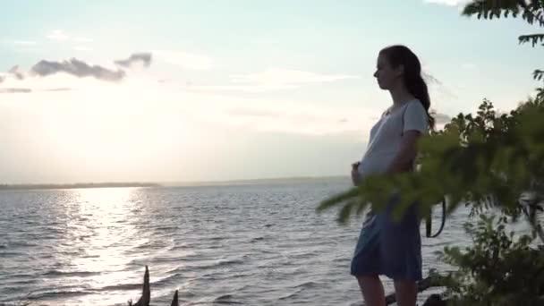 Těhotná žena dotýká její břicho na sunset.close-up těhotné ženy v pruhované šaty na pozadí řeka