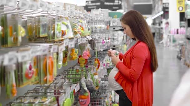 Giovane donna sceglie il giocattolo del bambino del supermercato, madre sceglie giocattolo per il loro bambino nel mercato, ragazza si leva in piedi vicino alla mensola del supermercato e seleziona i giocattoli babys