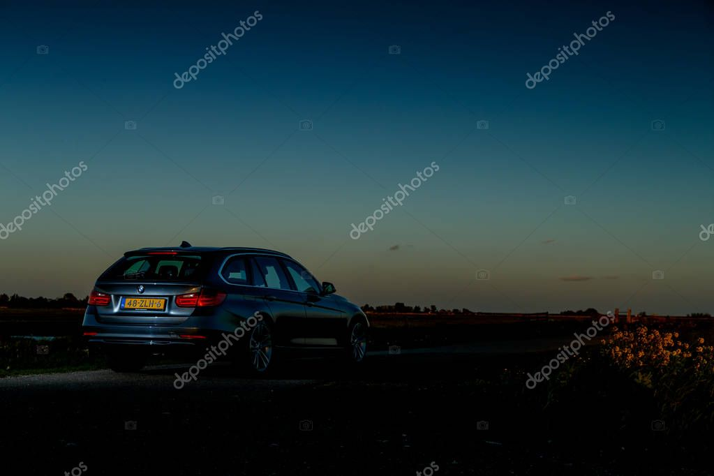 NETHERLANDS - 8 MAY, 2017: BMW 320i touring standing in a Dutch polder in a sunset.