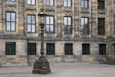 Streetlight near the Royal Palace of Amsterdam on the Dam Square. The palace was built as a city hall during the Dutch Golden Age in the 17th century.