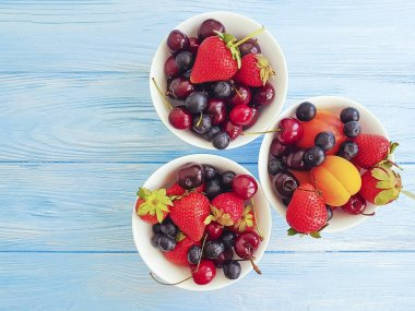 strawberry, cherry, blueberry, apricot on a wooden background