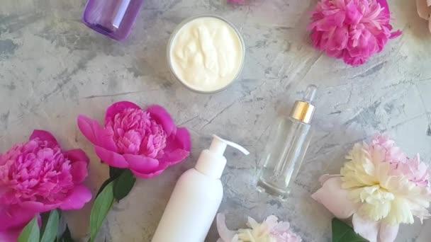 krém kozmetikai pünkösdi rózsa virág a szürke beton háttér lassú mozgás