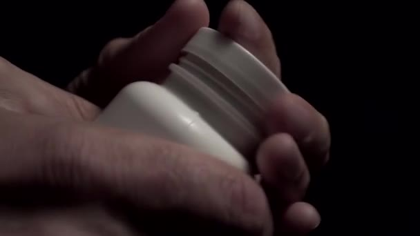 Hands opening a jar of pills and pouring out in a palm closeup