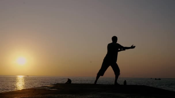 Man doing Chinese exercises Tai Chi Chuan on a pier at sunset