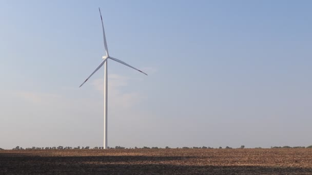 Větrná turbína na poli. Prázdné pole v popředí, modrá obloha na pozadí. Alternativní zdroj energie, produkce a výroba elektřiny. Koncepce ekologie a svobody
