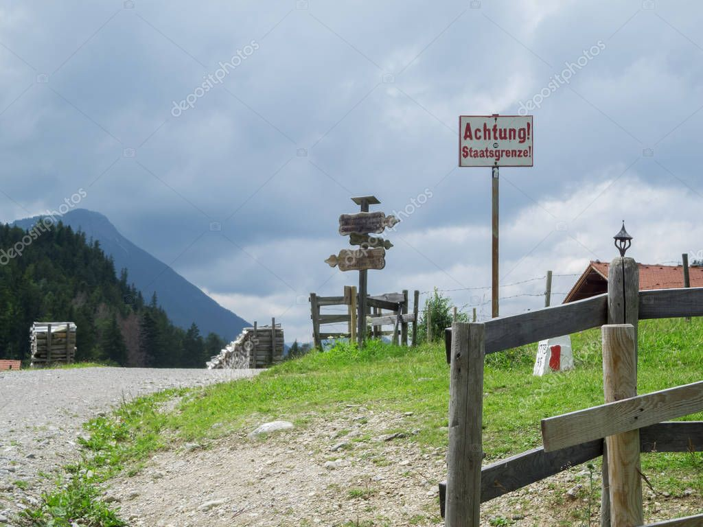 Border sign and landmark with weathered wooden signposts between Germany and Austria in summer at the Salober Alm at cloudy sky.