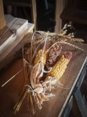 Fotografia Getrocknete Maiskolben auf einem Holztisch liegend.