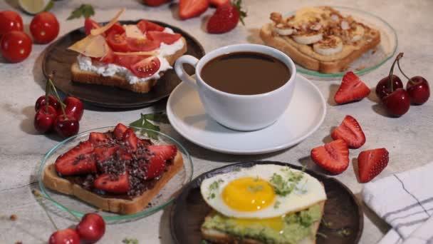 Reggeli különböző pirítós bogyókkal, sajttal, tojással és gyümölccsel, szürke háttérrel. A reggelizőasztal fogalma.
