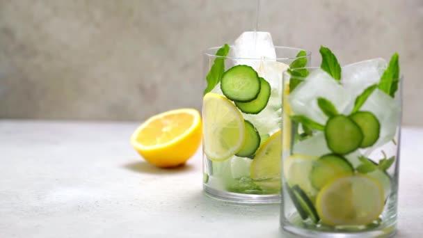 Detox drzá voda s okurkou a citrónem ve skle, světlé pozadí.