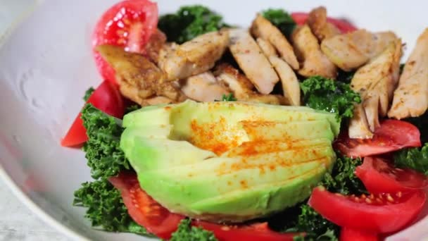 Chicken salad with tomato, avocado and kale in gray bowl. Diet food concept.