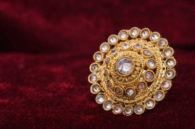 Fancy designer precious jewelry golden ring closeup macro image on red background for woman