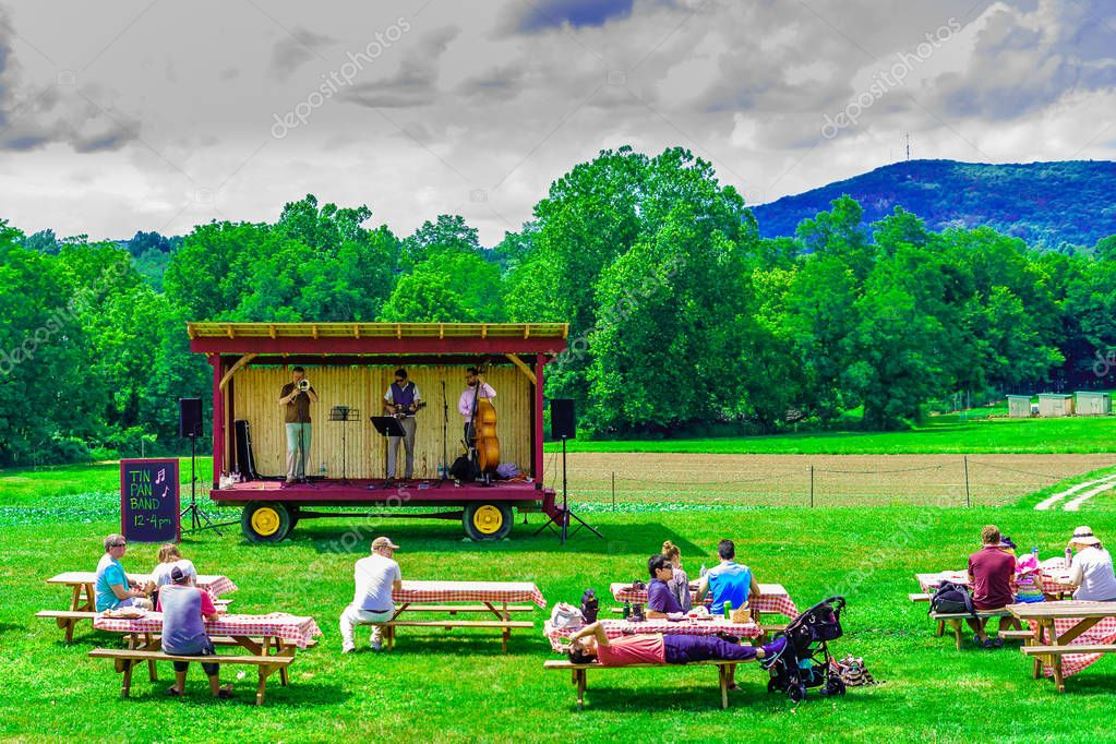Upstate New York USA - August 12, 2017 Country music band on platform Green field, landscape of meadow with grass US