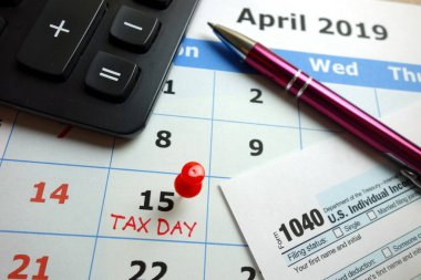 Tax day marked on April 2019 monthly calendar with 1040 form, pen and calculator