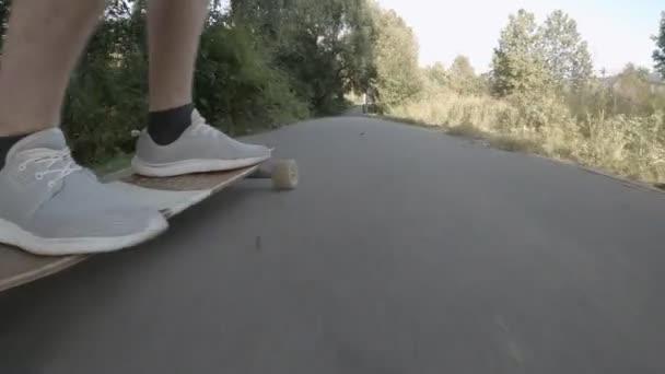 Teenager in grauen Turnschuhen und kurzen Hosen fährt an sonnigen Urlaubstagen Longboard auf Fußgängerstraße.