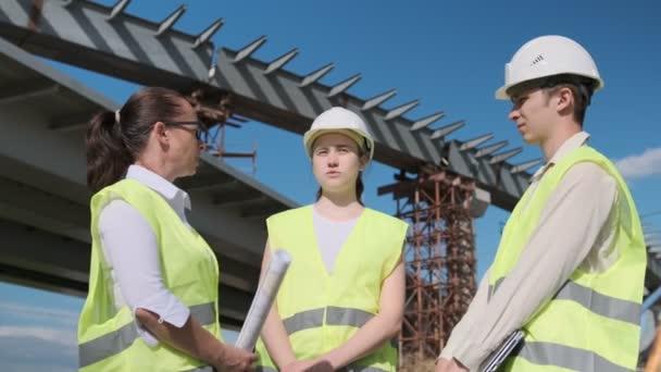 muž a dvě ženy architekti nebo inženýři mluví na staveništi na pozadí kovové konstrukce silničního mostu.