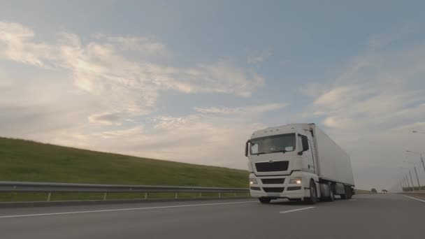 White truck with trailer driving on road, cargo transportation.