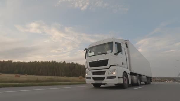 Bílý kamion s přívěsem řízení na silnici, nákladní doprava.