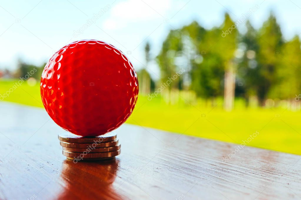 Golf red ball on a pile of coins, green grass field and blue sky background. Macro view, luxury sport game concept.