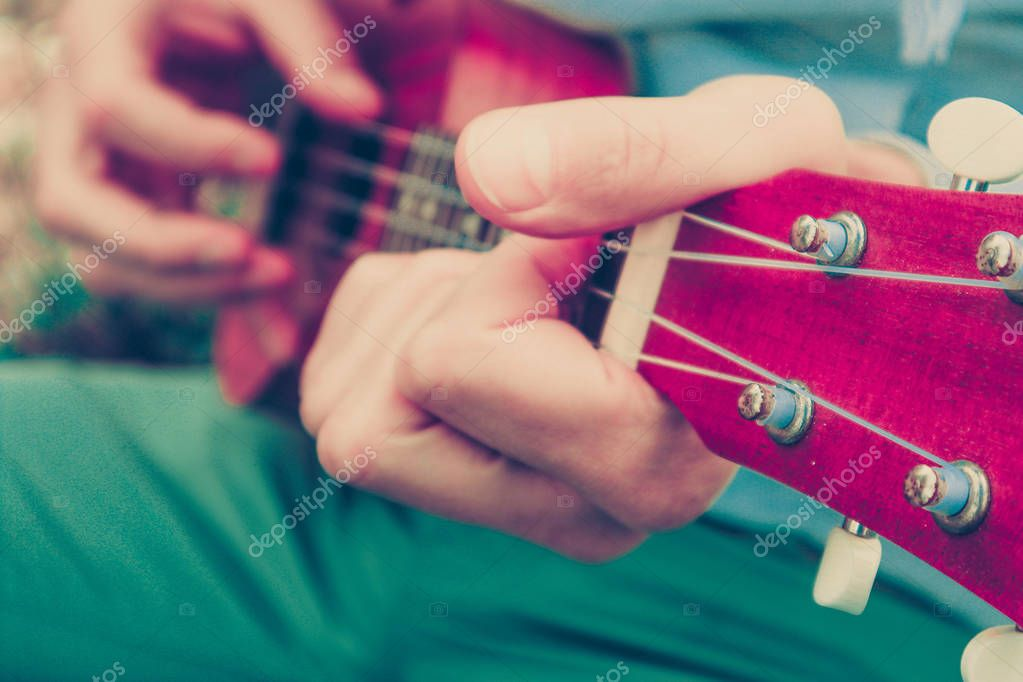 Photo depicts musical instrument ukulele guitar in the hands of player. Musician fingers are playing on the small ukulele guitar. Strings close up, macro view.