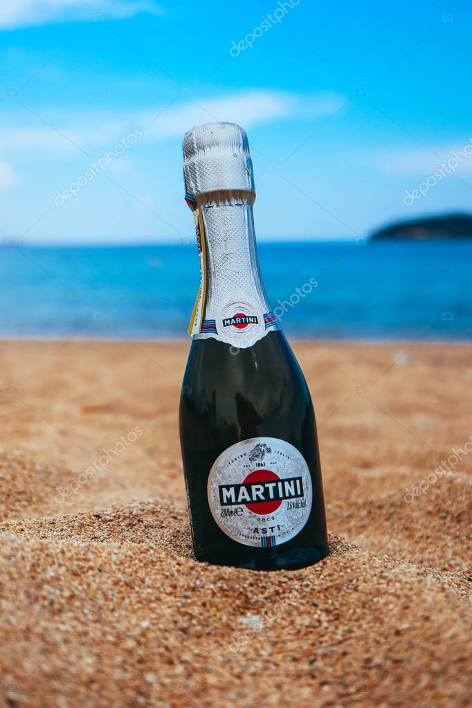 Greece, Kavala - May 1, 2018: A bottle of Martini champagne, sea beach on the background.