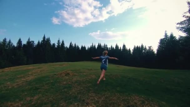 happy girl is running on a glade in the mountains