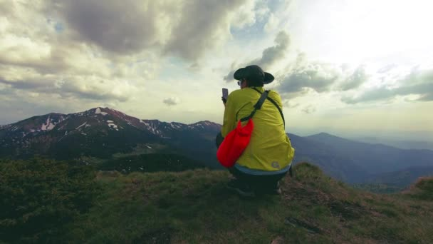 a tourist photographs a stunning mountain landscape