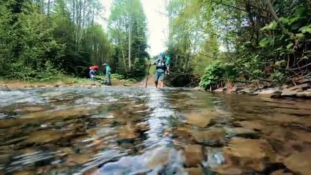 skupina cestujících přes řeku v lese