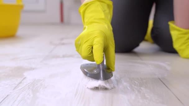 Žena ve žlutých gumových rukavicích s plastovým umyvadlem s vodou, pěnivým pracím prostředkem a štětcem čistí dlaždice na podlaze, přední pohled, zblízka. Dezinfekce povrchů, všeobecné čištění domu.