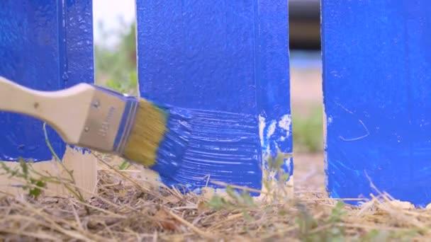 Handyman maluje dno desky z dřevěného plotu štětcem a modrým barvivem ve vesnici, zblízka. Opravy a stavební práce na pozemku