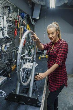 Female technician in her bicycle repair shop. Female Bicycle Mechanic. Woman repairing bicycle in garage. Technician woman fixing bicycle in repair shop