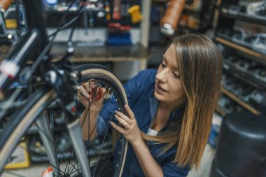 Repairing her bike. Woman fixing her bicycle. Girl working on her bicycle. Female Bicycle Mechanic. Young woman repairing a bike. Beauty at work