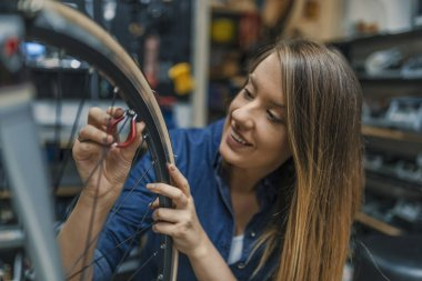 Making some adjustments to her bike. Girls can fix things too. Female Bicycle Mechanic. Young woman repairing bicycle. Repairing bicycle