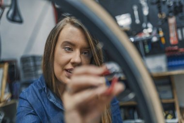 Focused On Tightening Bicycle Tire. Watchful technician mending the bicycle in the repair shop. Girl repair bicycle wheel. Woman bike mechanic working on bicycle