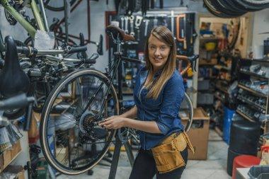 Cycling season coming soon. Female bicycle mechanic repairing bicycle. Female technician in her bicycle repair shop. Mechanic repairing gears of bicycle