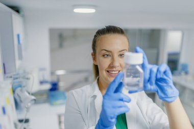 Young female lab technician conducting science researching. Female researcher carrying out research experiments in a chemistry lab. One female scientist researcher making research in chemistry laboratory