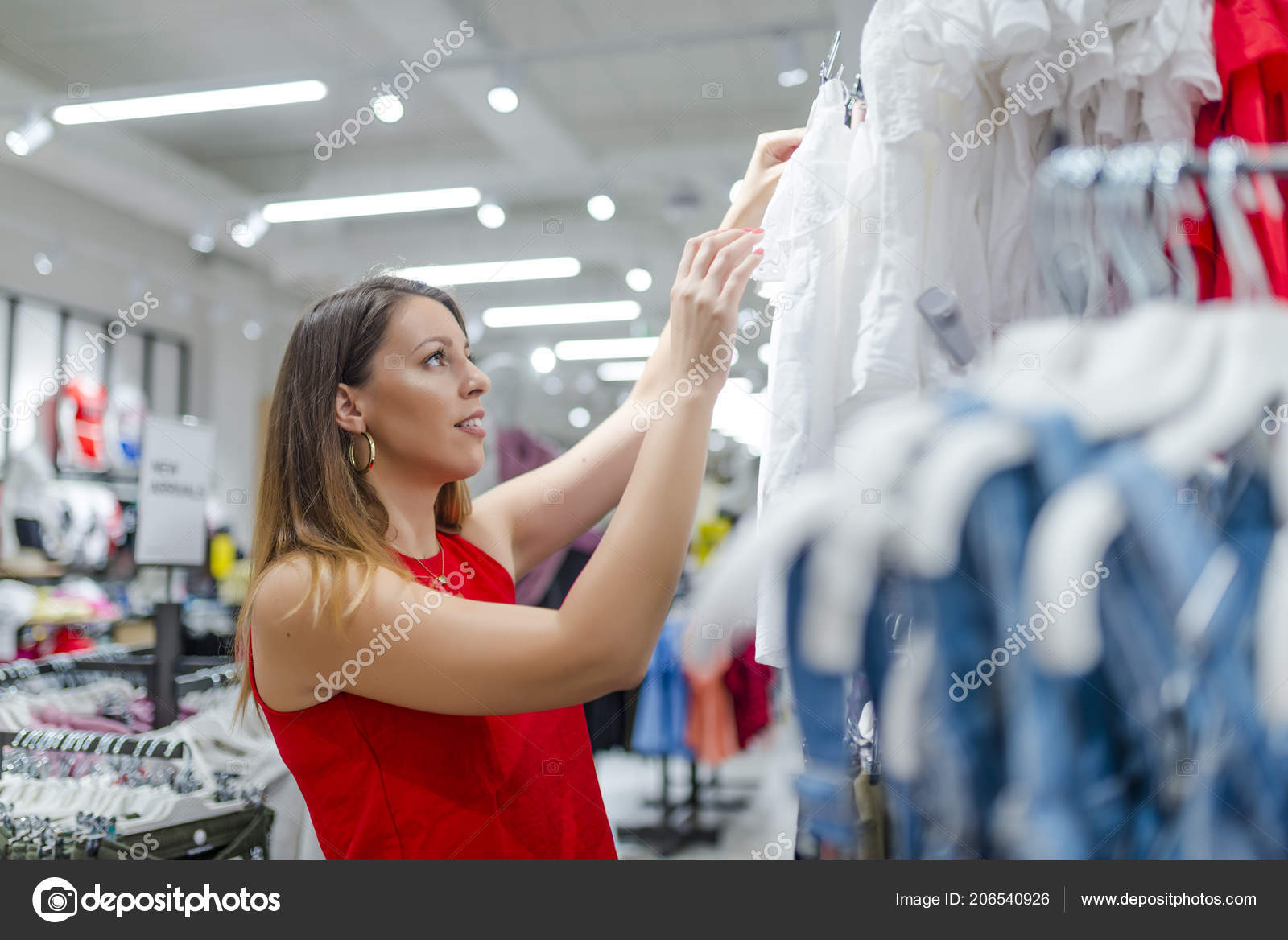 7b69a5f7a69 Half Body Shot of a Happy Young Woman with Shoulder Bag Looking at Clothes  Hanging on the Rail Inside the Clothing Shop. Woman shopper customer  choosing ...