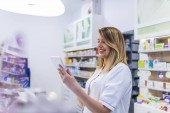 Fotografie Female pharmacist searching for medication while using digital tablet at drugstore