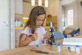Confident little girl uses microscope at home. Beautiful elementary schoolgirl uses a microscope for science project. Little girl concentrates while using microscope