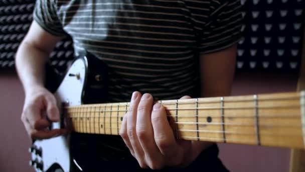 Hudebník hraje na kytaru elektro v ateliéru.