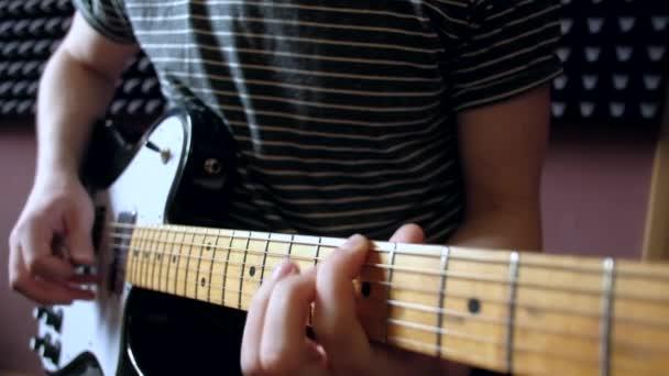 Hudebník hraje na kytaru elektro v ateliéru