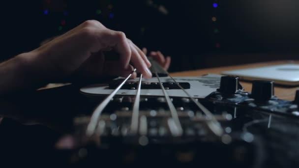 Hudebník hraje na baskytaru v ateliéru.