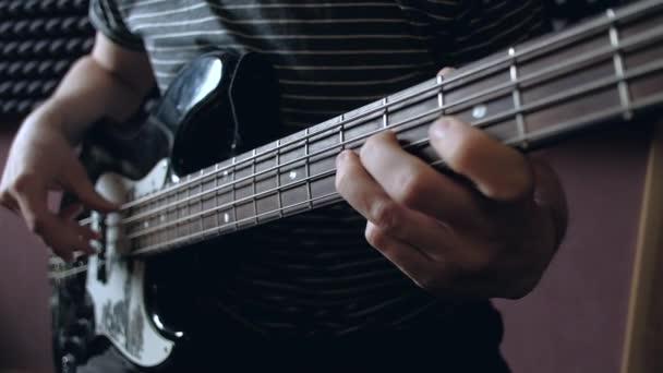 Zenész játszik basszus gitár a stúdióban.