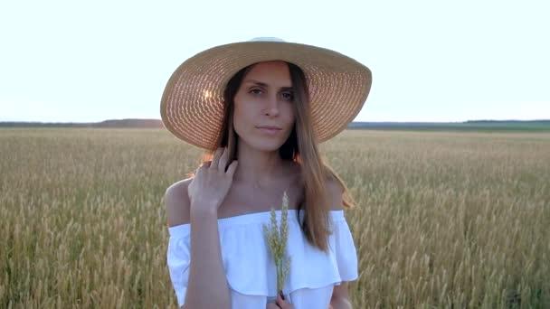 amazing portrait of beautiful woman standing in field of ripe golden wheat