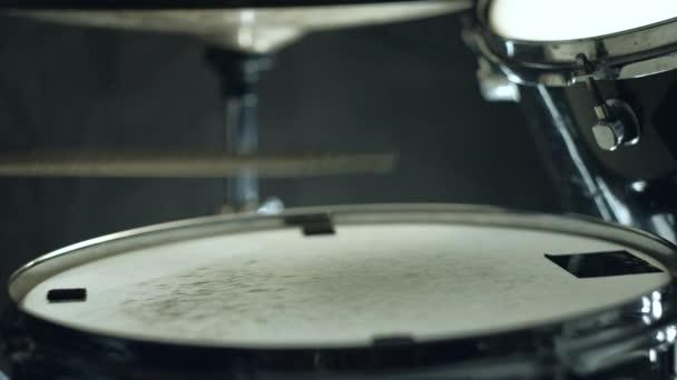 Jazzový bubeník hraje na bicí na koncert izolované na černém pozadí.
